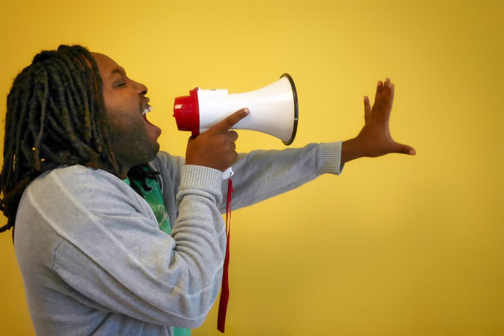 man speaking into a megaphone to avoid overuse