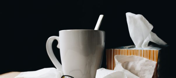tissue box and crumple tissues on a desk with a mug and glasses - how sickness affects the voice